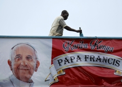 A volunteer paints the wall near a banner of Pope Francis at at the University of Nairobi grounds ahead of the Papal Mass in Kenya's capital Nairobi, on November 24, 2015. Photo courtesy of REUTERS/Thomas Mukoya *Editors: This photo may only be republished with RNS-POPE-AFRICA, originally transmitted on Nov. 24, 2015.
